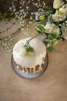 Easter cake decorated by white glaze and spring flowers