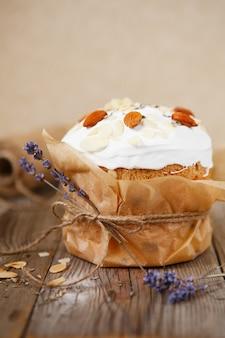 소박한 나무에 아몬드 꽃잎과 마른 라벤더로 장식 된 부활절 케이크