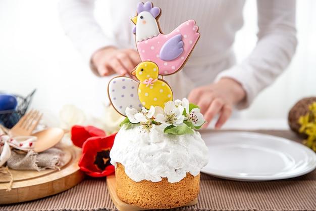 花で飾られたイースターケーキとお祝いのテーブルの明るいディテール。イースターのお祝いのコンセプト。