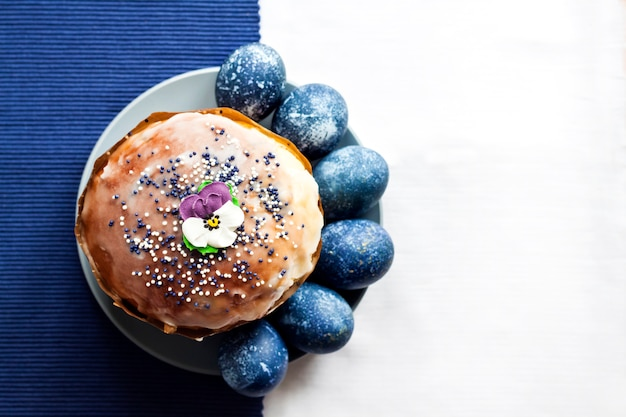 Пасхальный кулич украшен сахарным цветком и яйцами синего цвета на тарелке на белой и голубой тканевой поверхности