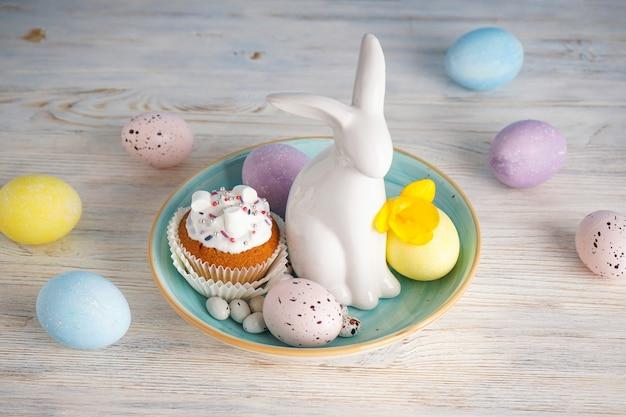 Кулич, пасхальный кролик и яйца с цветком на деревянном фоне.