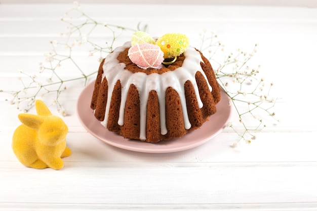 Easter cake and and easter bunny on a white wooden desk