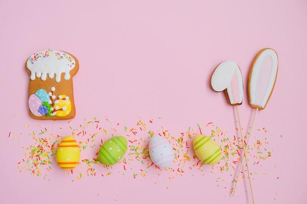Easter cake, eggs, sugar sprinkles and cookies bunny ears