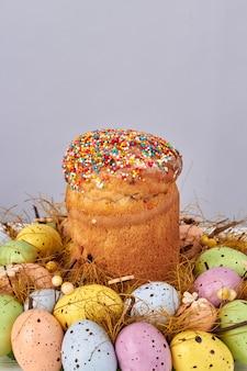 色付きの卵の山のイースターケーキ。垂直ショットのクローズアップ。
