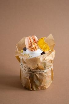ベージュの壁に分離されたイースターケーキ、クローズアップビュー。チョコレートチップ、メレンゲ、マカロニ、スイートオレンジで飾られた伝統的なイースターケーキ。