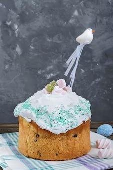イースターケーキ-木製のテーブルにメレンゲで飾られたドライフルーツのクリーチ。甘いお祝いパン。伝統的なイースターのベーキング。