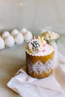 Кулич на фоне куриных яиц и муки. рецепт сладкого торта.