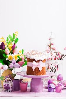 Пасхальный кулич на подставке для торта и цветы, сиреневые украшения на переднем плане с копией пространства