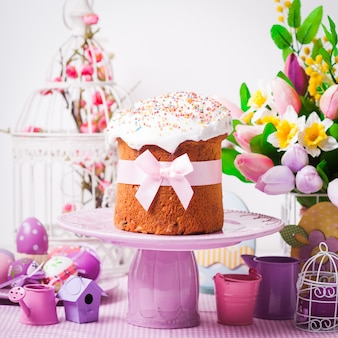 Пасхальный кулич на подставке для торта и цветы, сиреневые украшения на переднем плане