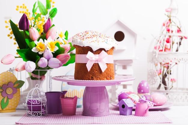 Кулич на подставке для торта и цветы, сиреневые украшения на переднем плане