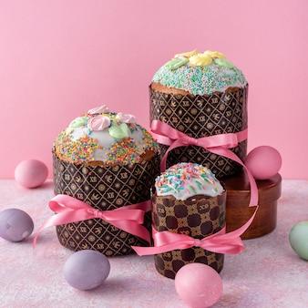 Пасхальный кулич, крашеные яйца на розовом фоне.