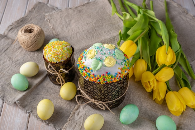 Easter cake, painted eggs with tulips on a wooden old rustic background.