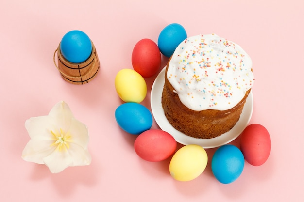 Easter cake on a plate with colorful easter eggs and a tulip flower on the pink surface