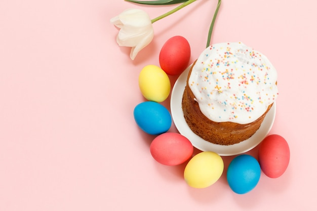 Easter cake on a plate with a tulip flower and colorful easter eggs on the pink surface