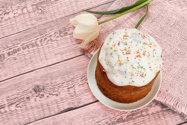 Easter cake on a plate with a tulip flower on the pink sackcloth and boards