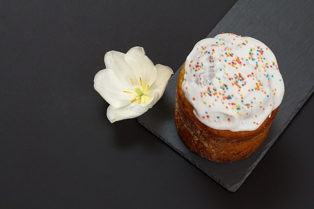 Easter cake on a stone cutting board with a tulip flower on the black surface