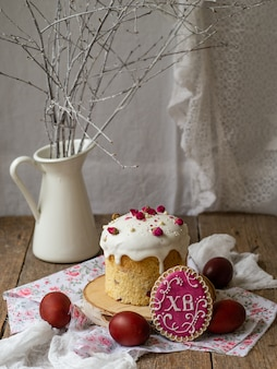 Easter cake. traditional easter sweet bread decorated meringue, pink dry roses, red eggs and cookies in form of easter eggs on wooden background with white branches. copy space, selective focus