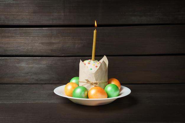 暗いテーブルの上に色付きの卵が付いたイースターケーキ教会のキャンドルが燃えているケーキに挿入