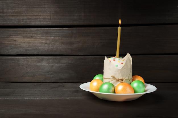 教会のろうそくが燃えている暗いテーブルの上の着色された塗られた卵がケーキに挿入されたイースターケーキ