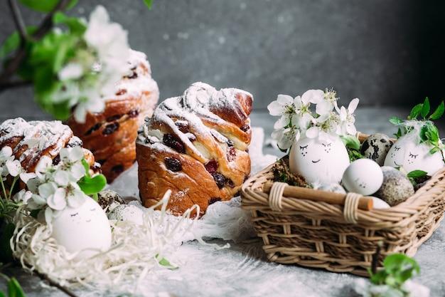 灰色の背景にイースターエッグと花を持つイースター ケーキ