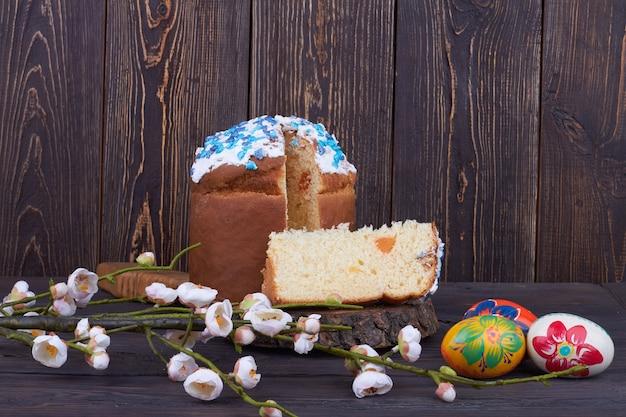 花と卵のイースターケーキ。暗い木製の背景に静物画。