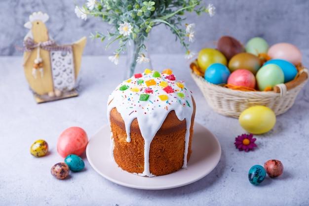 회색 배경에 과일과 색된 계란과 꽃과 부활절 케이크