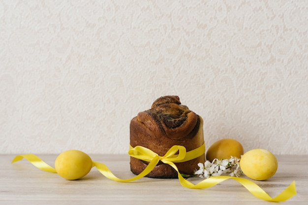 Easter cake, yellow painted eggs and flowers on a beige table. spring holiday season. traditional festive table. copy space