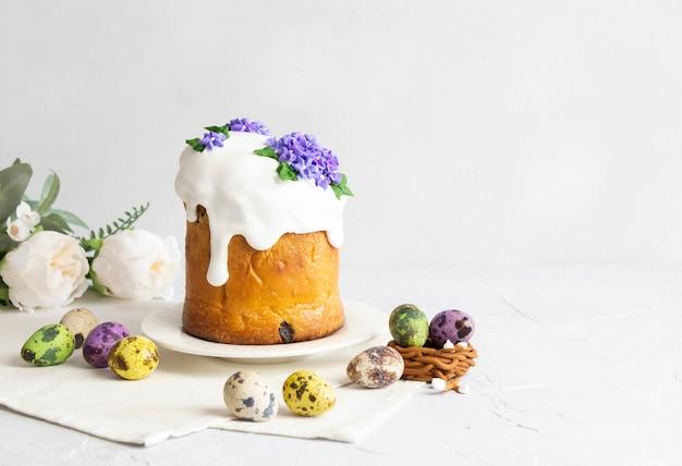 Пасхальные куличи и красочная композиция яиц на белом фоне с копией пространства