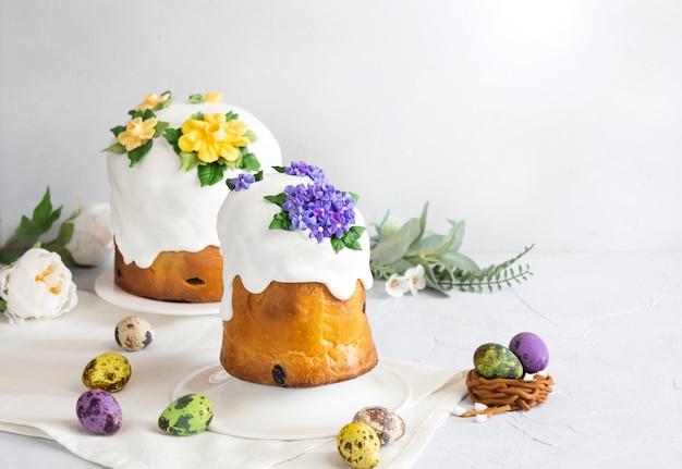 Пасхальные куличи и красочная композиция из яиц на белом фоне
