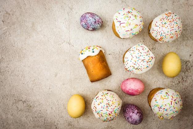 Куличи и крашеные пасхальные яйца на красивом фоне. религиозный праздник светлой пасхи.