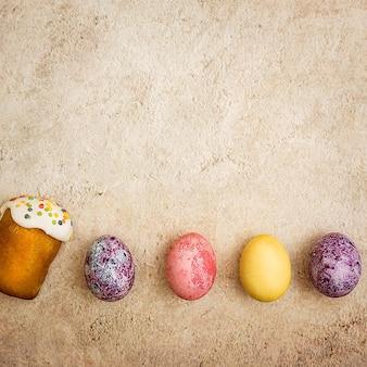美しい背景にイースターケーキとイースター色の卵。明るいイースターの宗教的な祝日。
