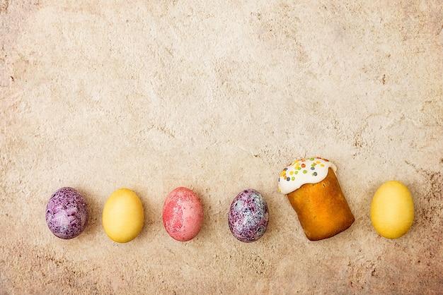 美しい質感の背景にイースターケーキとイースター色の卵。