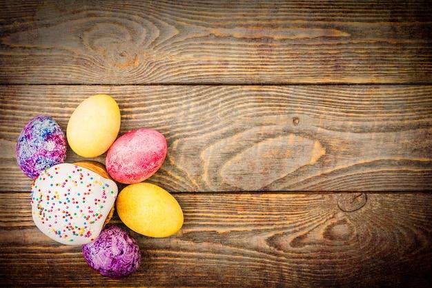 木製の背景にイースターケーキとイースター色の卵。