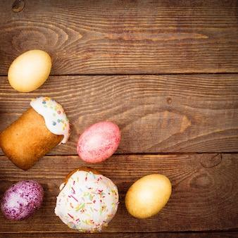 木製の背景にイースターケーキとイースター色の卵