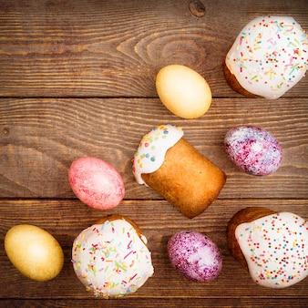 木製の表面にイースターケーキとイースター色の卵。明るいイースターの宗教的な祝日。