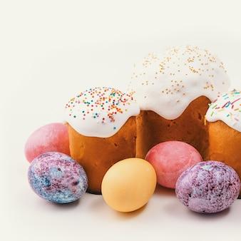 Куличи и пасхальные крашеные яйца на изолированной белой предпосылке.