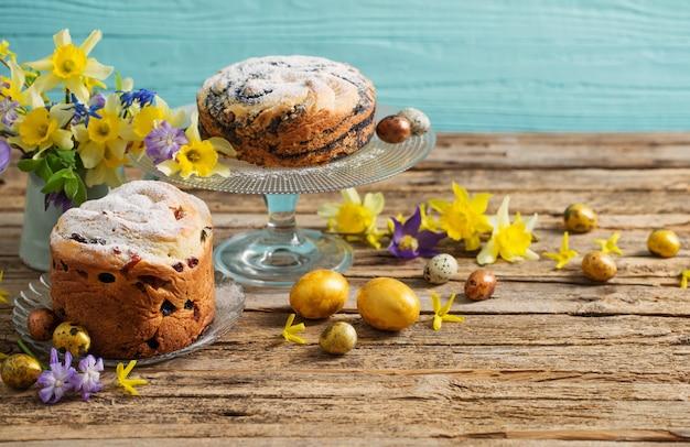 青い木製の背景にイースターケーキと卵