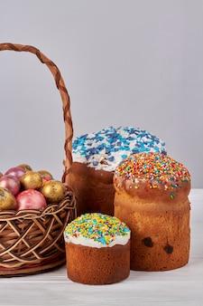 イースターケーキと卵。装飾的なイースターエッグとアイシングのケーキでいっぱいの籐のバスケット。