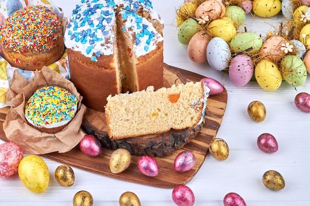 Куличи и крашеные яйца на деревянной доске. традиционная православная христианская пасхальная еда.