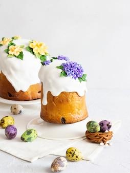 Куличи глазированные, украшенные цветами и красочной композицией яиц на белом фоне