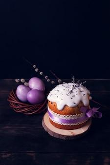 Куличи на a, украшенные лавандой и зефиром, и расписные пасхальные яйца в плетеном гнезде.