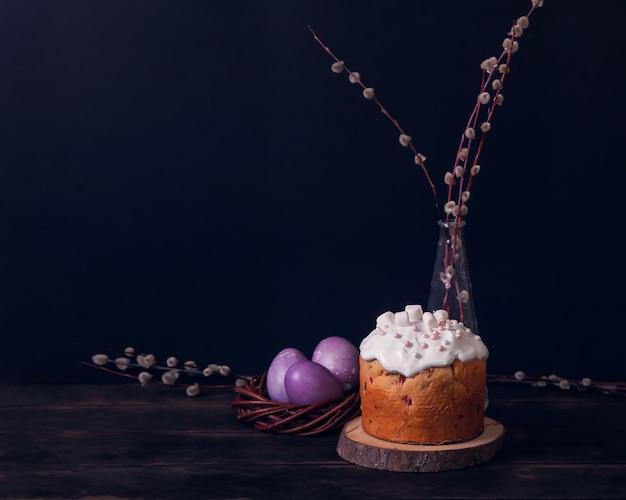 Куличи на a, украшенные зефиром и крашеные пасхальные яйца в плетеном гнезде.