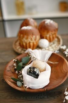 Куличи на столе. пасхальные яйца на деревянной тарелке. подготовка к пасхе.