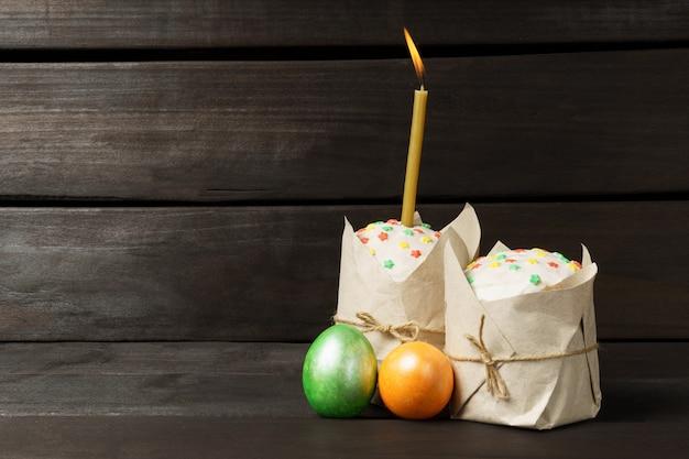 暗いテーブルの上の着色された色の卵とイースターケーキ