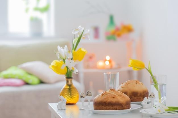 白いインテリアの春の花とイースターケーキ