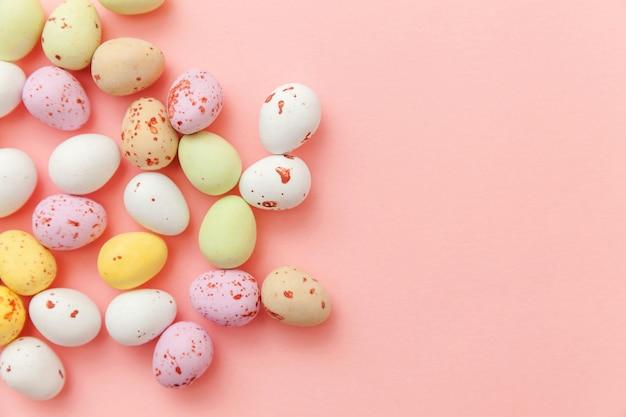 ピンクの背景に分離されたイースターキャンディチョコレート卵とジェリービーンズのお菓子