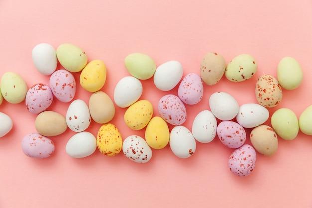 ピンクのテーブルに分離されたイースターキャンディチョコレートの卵とジェリービーンズのお菓子