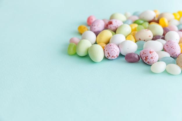 トレンディなパステルブルーの背景に分離されたイースターキャンディチョコレートの卵とジェリービーンズのお菓子