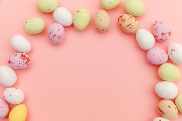 Пасхальные конфеты, шоколадные яйца и желейные конфеты, изолированные на модном пастельно-розовом фоне