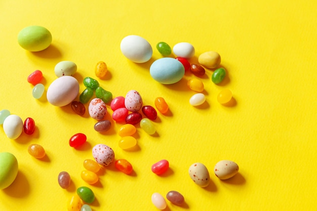 トレンディな黄色の背景に分離されたイースターキャンディチョコレート卵とジェリービーンズのお菓子